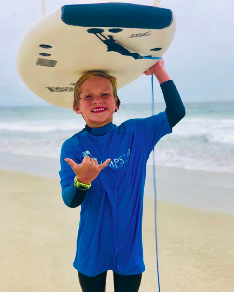Kid holding surfboard
